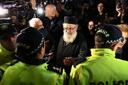 En präst pratar med polismän vid biopremiären av 'And then we danced' i Tbilisi, Georgiens huvudstad.
