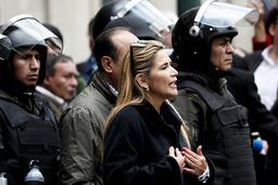 Bolivias interimspresident Jeanine Áñez talar med poliser framför presidentpalatset i La Paz.