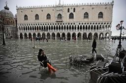 En kvinna har slagit sig ner på en stol vid vattenmassorna på Markusplatsen i Venedig på onsdagen.
