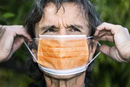 Ett kirurgiskt munskydd fästs oftast med ögla bakom öronen och är raka och veckade i längdriktningen. Arkivbild.