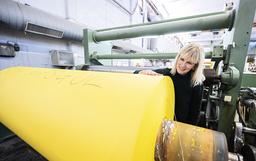 Lessebo Papers marknadschef Carina Jensen vid en rulle med rapsgult papper på Lessebo bruk i oktober 2020.
